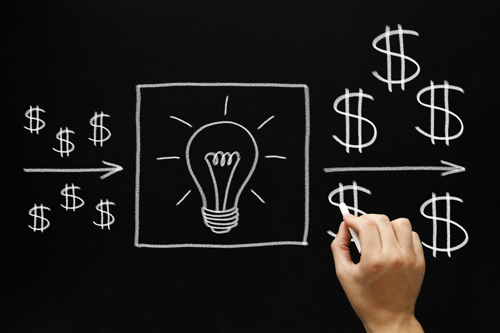 A blackboard with chalk writing shows small dollar signs going into a bright light bulb and coming out with large dollar signs to illustrate the concept of Return-On-Investment by using SEO for electrical contractors.
