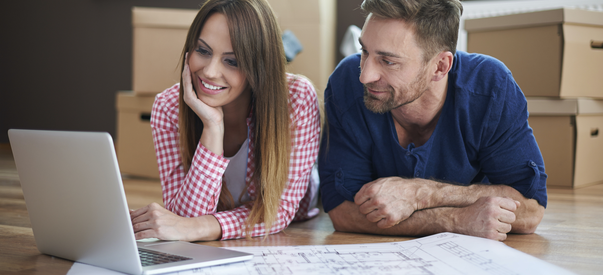 A young couple renovating their first home looks at blueprint and computer to find a local electrician.