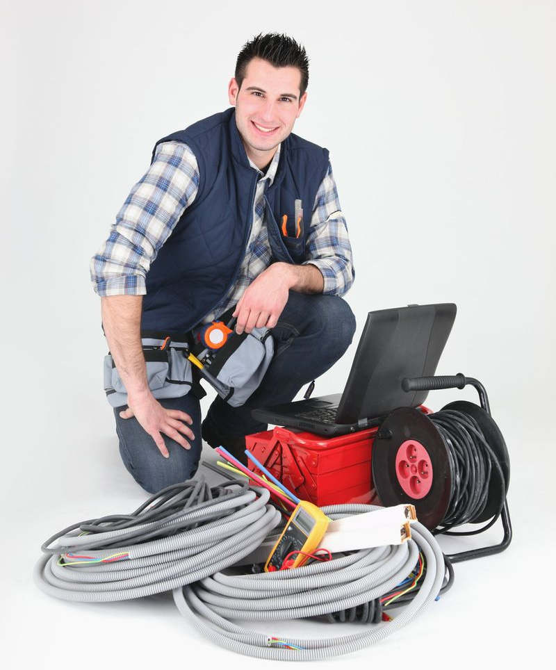 A smiling electrician with electrical equipment setting up for a new job